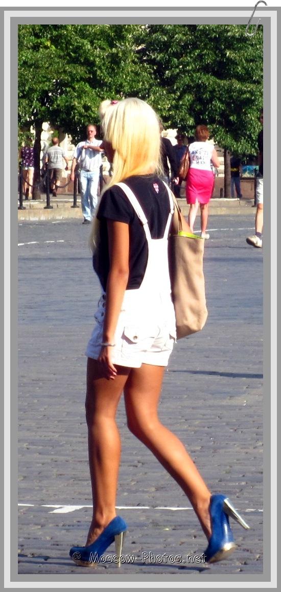 Blonde girl in white shortened summer overalls