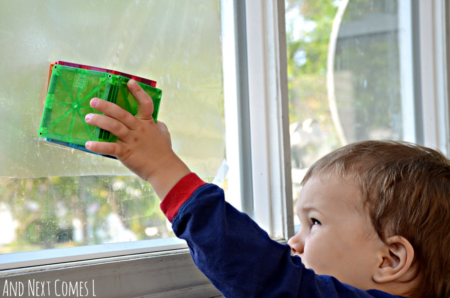 Checking out a cube made from Magna-Tiles on a window from And Next Comes L