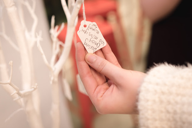 "picture of a hand holding a label with the words ""darling daisy, we miss you, love mummy xx"""