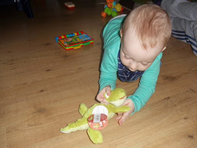 little boy kneeling up on floor playing with a soft toy