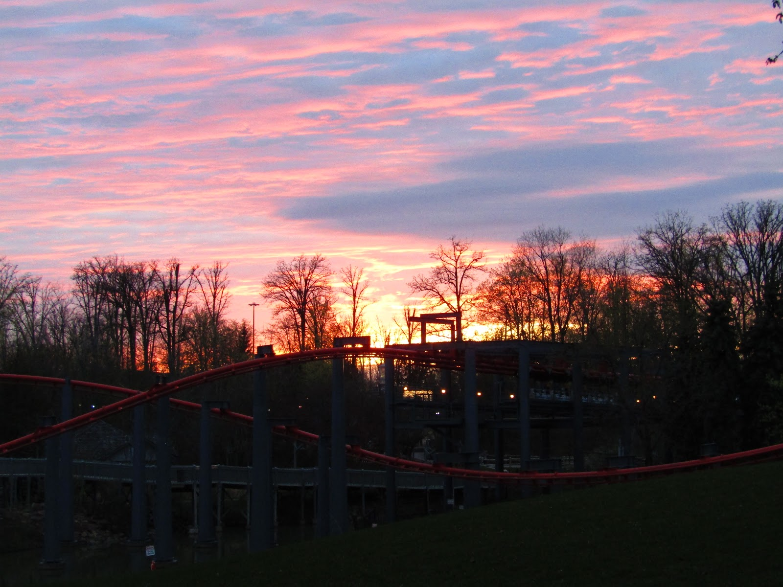 A beautiful sunset provides an orange glow on the beautiful landscape at Canada's Wonderland. The sky is orange and pink with some wavy clouds.