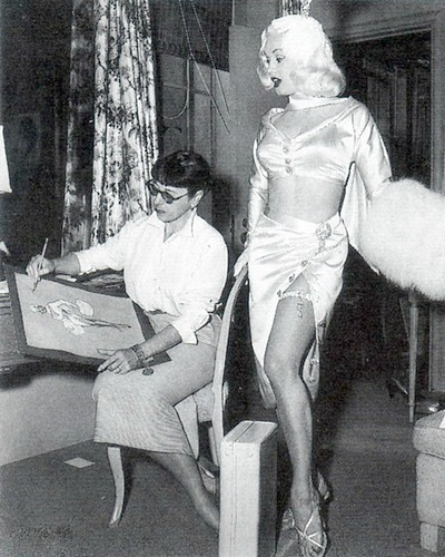 Edith Head sketching a design with Mamie Van Doren standing beside her