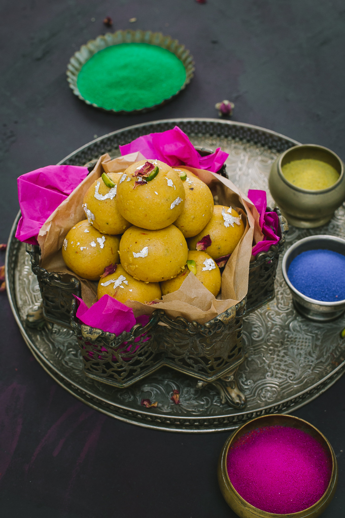Moong Dal Ladoo or Mung Daal Ladu is a wonderful classic Indian sweet, a treat for the eyes as much as it is to the taste buds. A mouthwatering moong or mung dal ladoo made from yellow split lentil flour in pure desi ghee and garnished with pistachio slivers and edible rose petals. These are simply moreish and must for all Indian festivities and celebrations such as Holi, Diwali, Raksha Bandhan or Ganesh Chaturthi!!