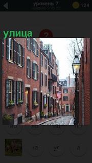 узкая улица города проходит между домами из красного крпича