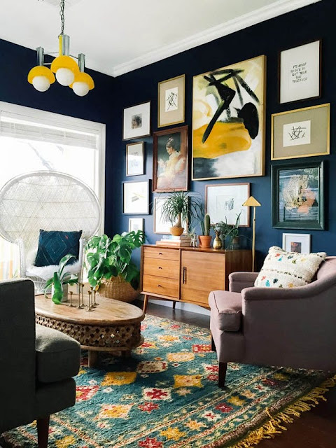 Dark green walls and art wall in living room on Hello Lovely