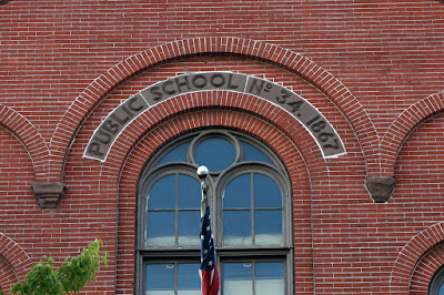 Terracotta plaque above top floor window reading Public School No. 34. 1867