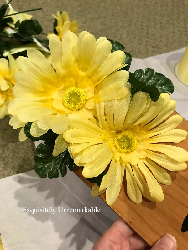 Yellow flowers and greenery glued to wooden fan blade