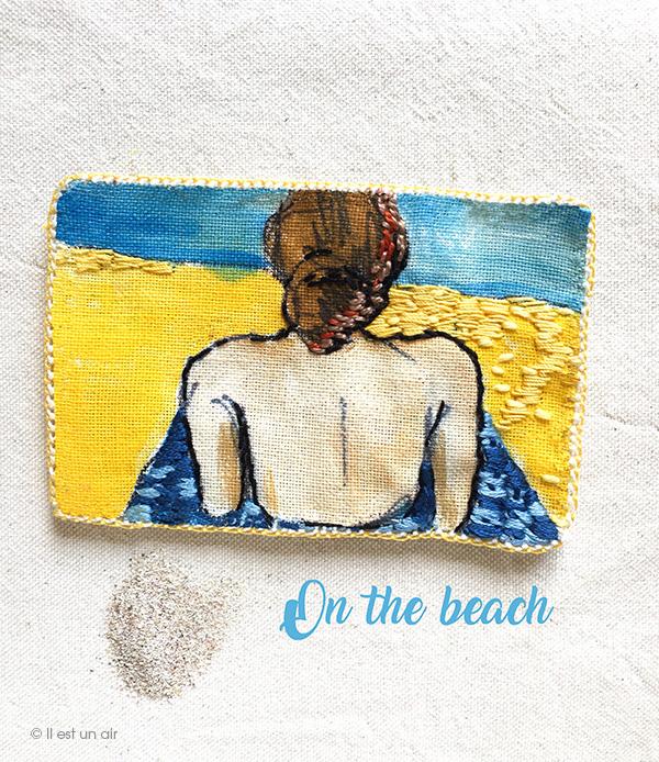 Broderie : femme allongée sur la plage