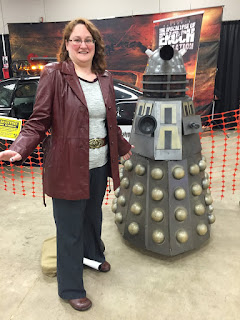 Photo of me cosplaying Donna Noble next to a model Dalek.