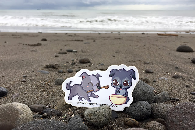 Small sticker of dogs on a black sand beach