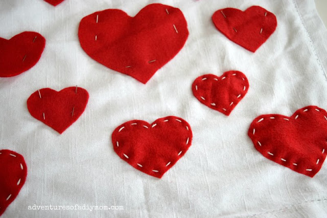 sew felt hearts to pillow with running stitch
