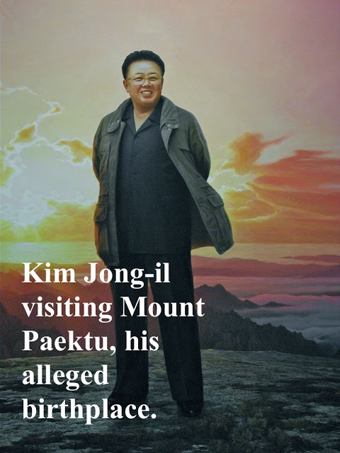 Stylized, propaganda painting. Kim Jong-il, portrayed as a semi-deity, standing on a mountain, sunset behind him. Mount Paektu, his alleged birthplace.