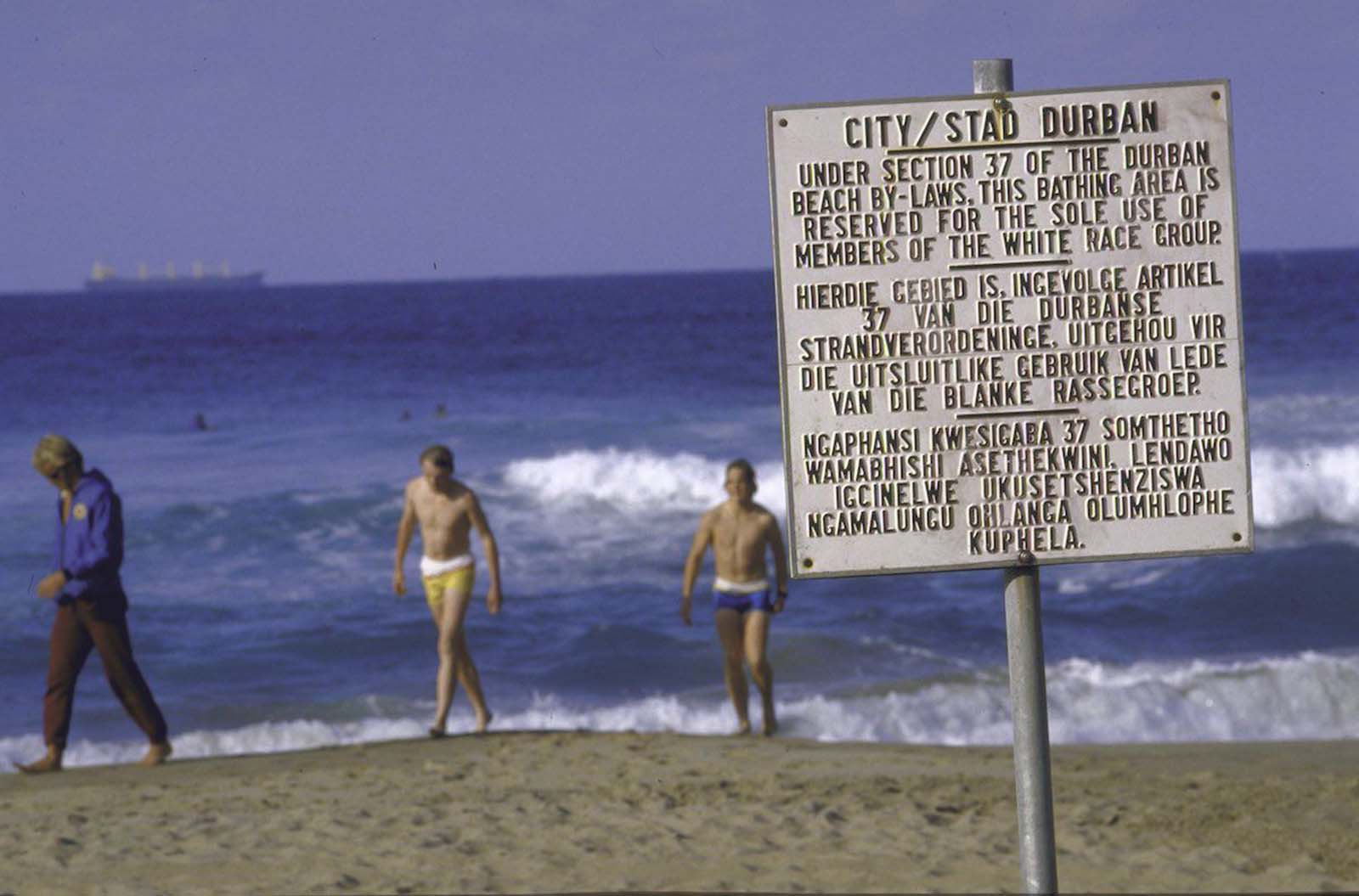 Whites only sign in foreground at restricted beach, with bathers in background. 1986.