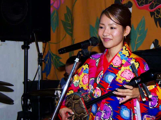 girl entertainer singing and playing a sanshin