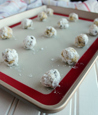 balls of cookie dough rolled in powdered sugar on tray ready to bake