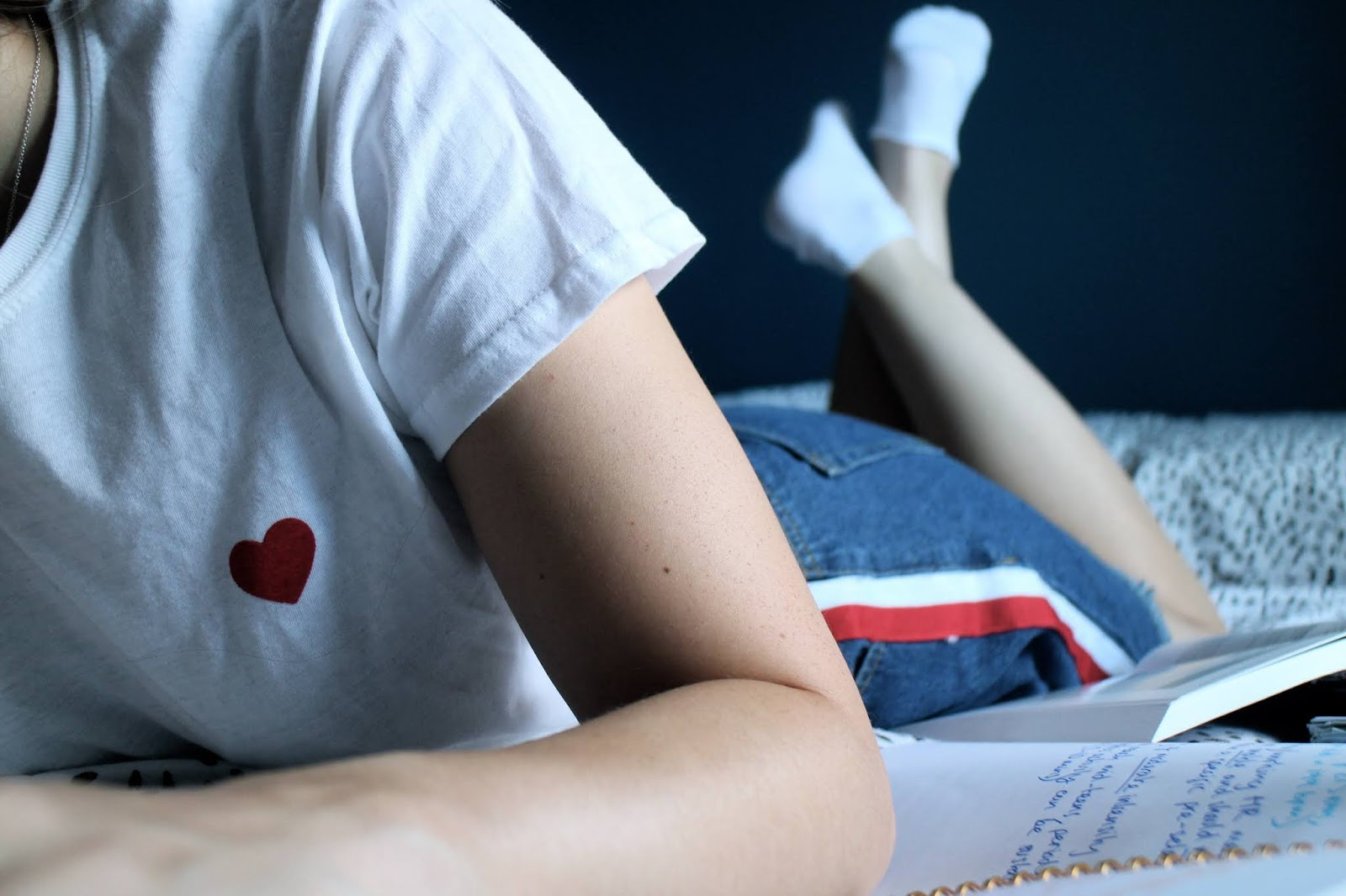 Close up of heart tee and denim skirt whilst laying on bed