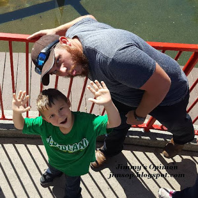Grandson Benjamin and his father Tim playing around while waiting in line at Legoland.