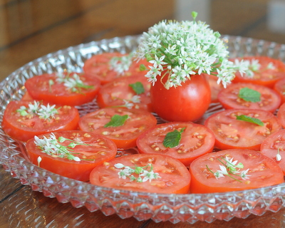 Sliced tomatoes with garlic chive flowers