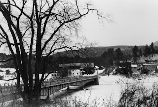 A black and white photograph of a bridge over a river.