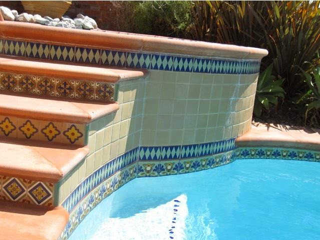 Hand-painted glazed ceramic deco tiles with terracotta pavers showcase the stairs, risers and the pool.