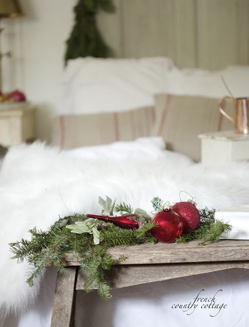 Ornaments and greenery on bench at foot of guest bed