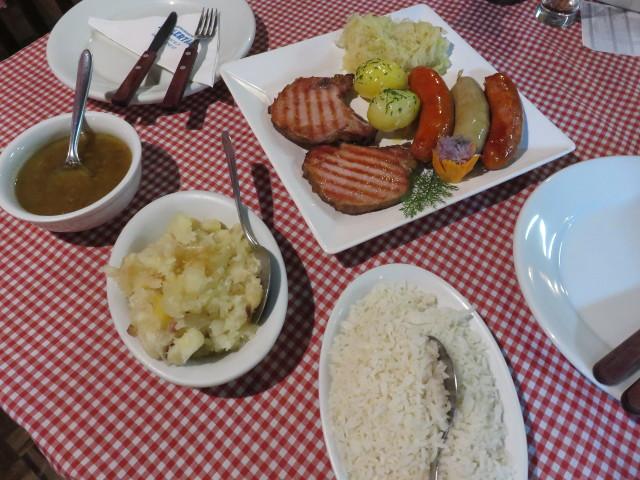 Schlachtplatte, a German meal with pork chop, sausages, rice, potato, Sauerkraut and cassava.