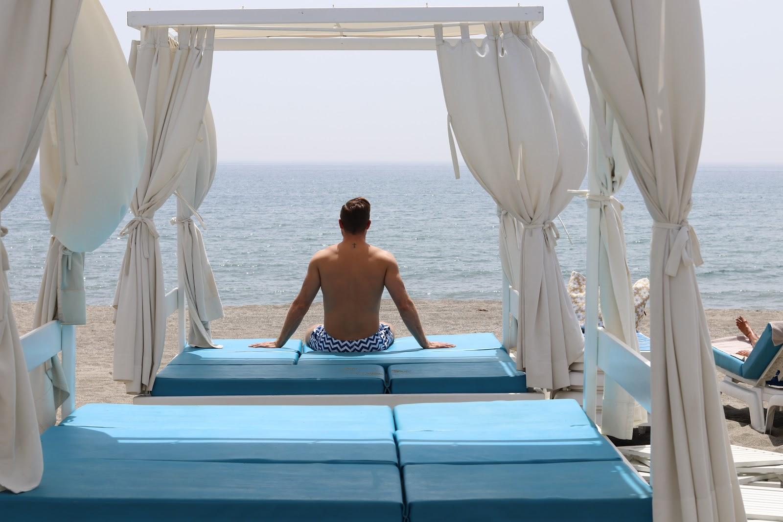 TwentyFirstCenturyGent, Ben Heath sunbathing with a cocktail on a White Day Bed at Chambao Beach Bar, Sotogrande, Spain