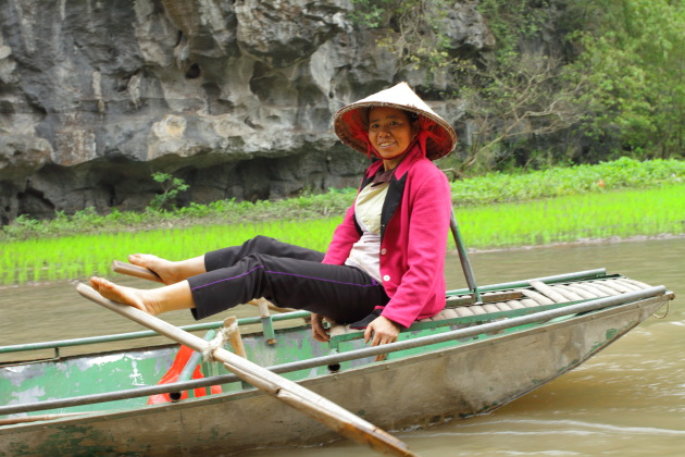 Vietnamese lady and her foot rowing boat at Tam Coc River, Ninh Binh, Vietnam