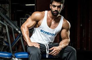 Hombre sentado en un bando de gimnasio