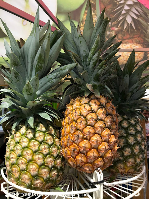 Three pineapples on a white fruit stand.