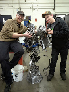 Randal Smith and Daniel Locke show off a sculpture they made out of a transmission they disassembled. A competing team had to take apart and reassemble the sculpture back into a working transmission. (Photo courtesy Darrin Marshall)