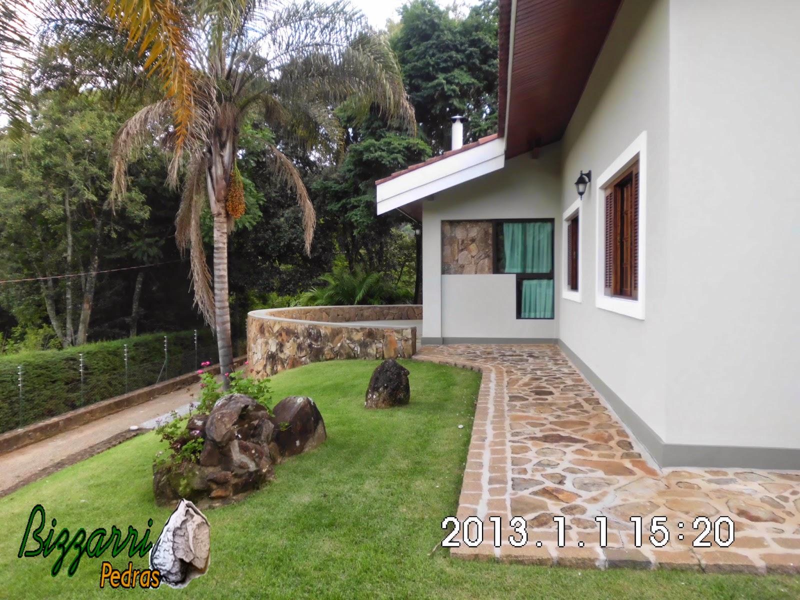 Calçamento com pedra rústica da calçada de pedra, com os muros de pedra, os bancos de pedra com a construção da residência com o paisagismo.
