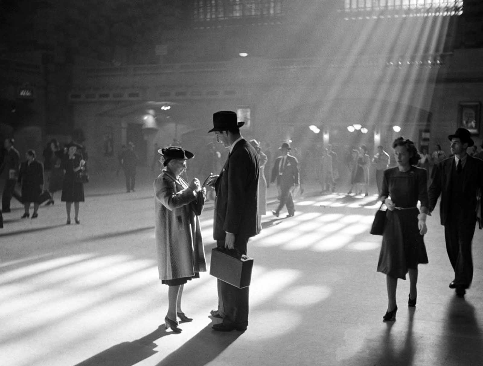 A man and woman talk together as people pass through the Main Concourse of New York's Grand Central Terminal in Midtown Manhattan, in October of 1941.