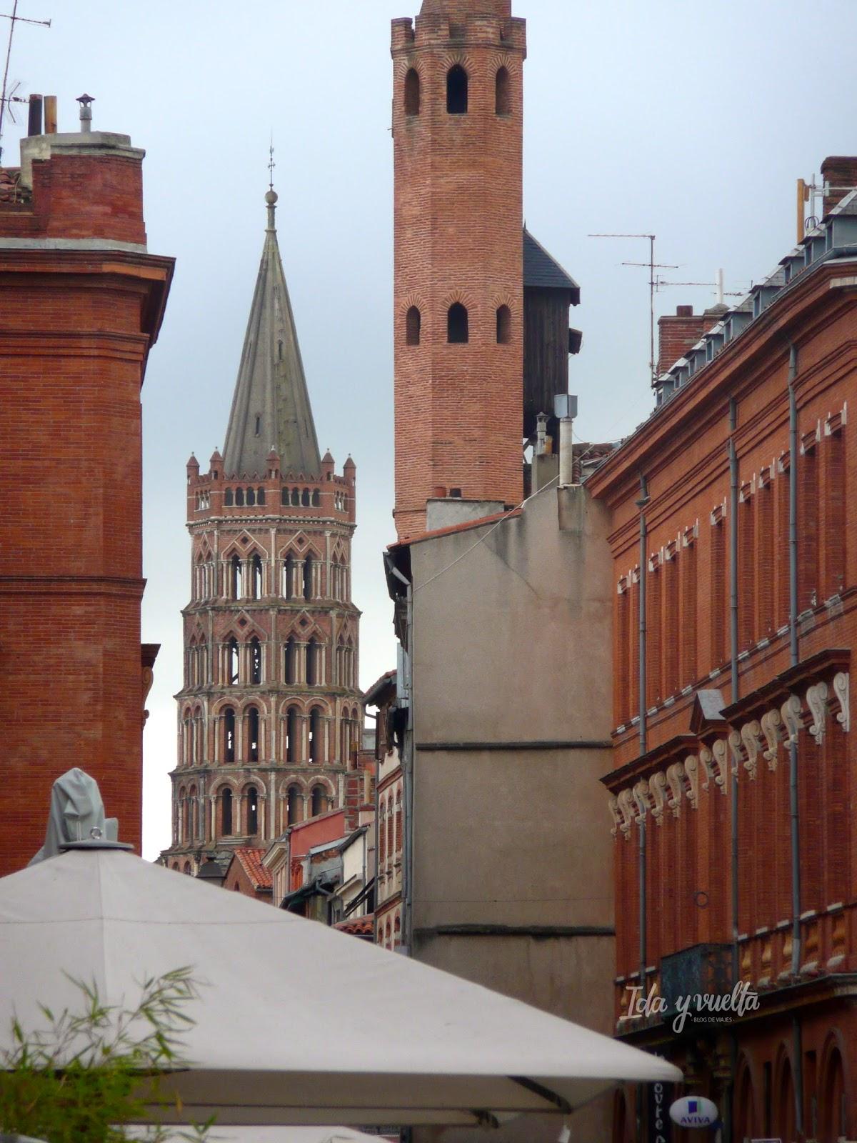 Edificios de ladrillo y St. Sernin al fondo