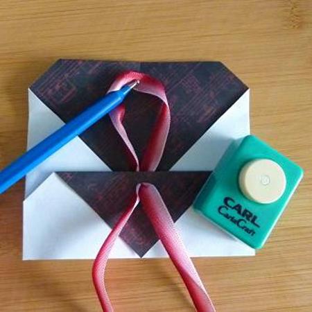 Threading ribbon through an envelope for fastening