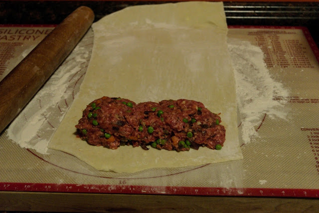 Formed meat mixture sitting at the base of the rolled out pastry dough.