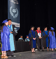 snapshot of 2017 ceremony.  President Bustamante posing for a photo with a student grad.
