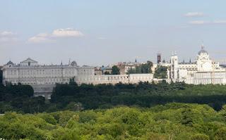 Vista del palacio y la catedral de la Almudena desde una colina de la Casa de Campo. Por medio, las copas de los árboles del parque.