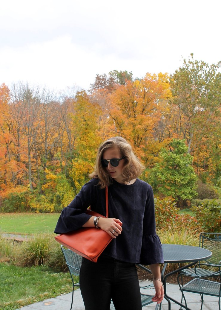 bell sleeve shirt, orange purse, black jeans for a cute Halloween outfit
