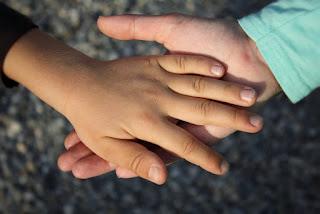 Auf dem Foto: eine Kinderhand legt sich vertrauensvoll in die eines Erwachsenen