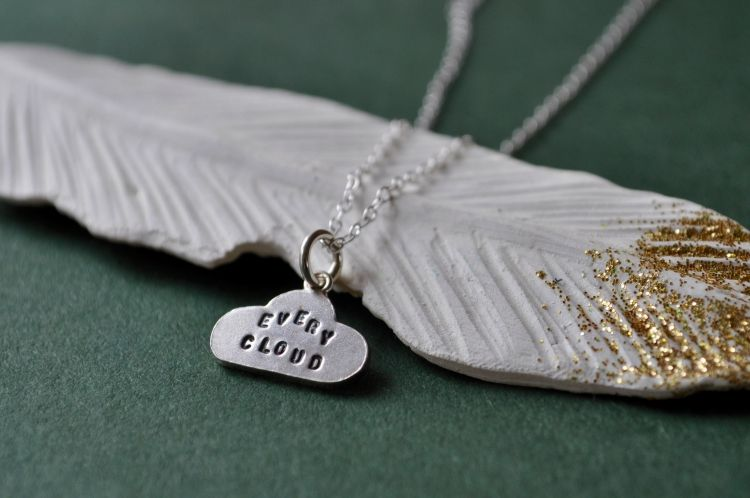 Silver Cloud Pendant set against a White and Gold Feather by The Silver Shed