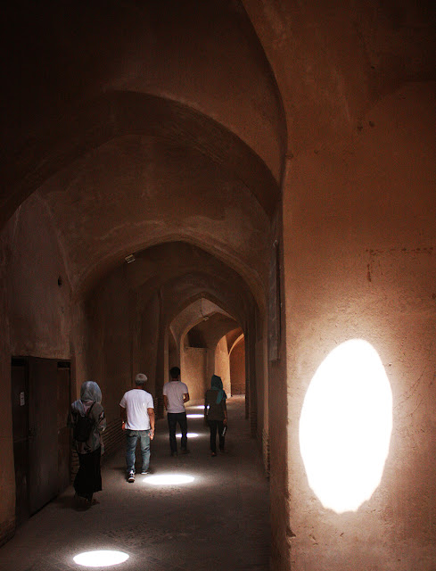 Travelers walking through a historical bazaar in Iran.
