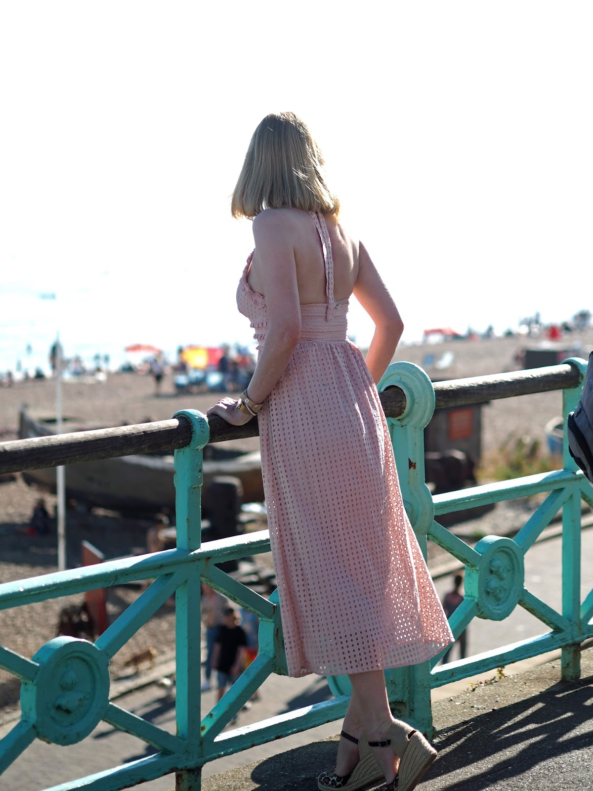 Back view of pink broderie anglaise ruffle halter neck midi dress with leopard print espadrilles