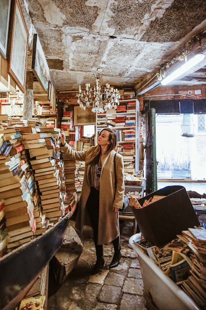 Alicia Mara in Venice, Italy surrounded by books