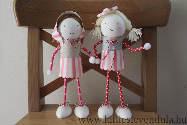 Dos muñequitas de cartón de pie sobre una silla de madera