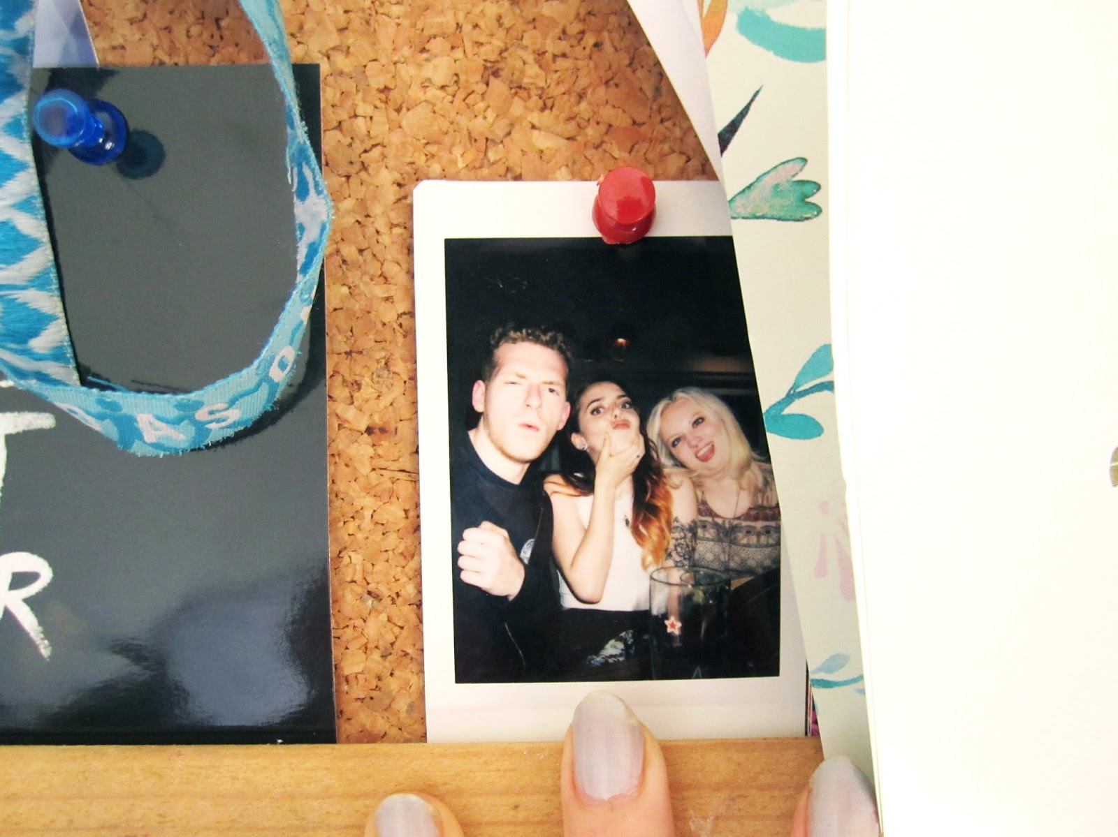 polaroid of friends on a cork  noticeboard