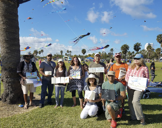 Group photo of of people holding their sketchbooks with the sky and kites in the background.