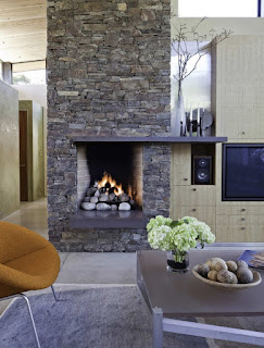 gorgeous stoned fireplace design plus brown armchair feats wooden table on cream rug idea