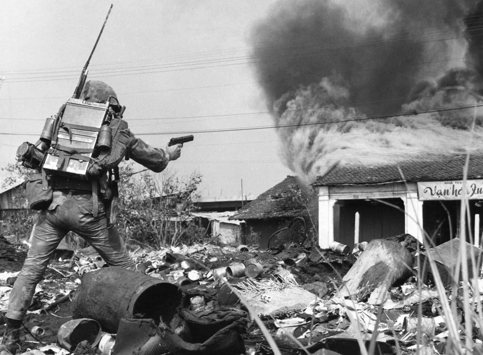 South Vietnamese combat police advance toward a burning building in northeastern Saigon on February 19, 1968, as they battle Viet Cong forces who had occupied several city blocks in the area.