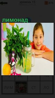 За столом сидит девочка и перед ней цветы и банка с лимонадом, рядом лимон
